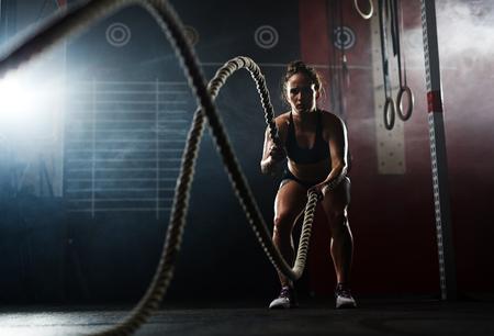 Fit vrouw swewating tijdens de training met touwen