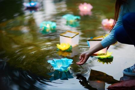 Traditionele feestelijke lelies met brandende kaarsen die op het rivieroppervlak drijven