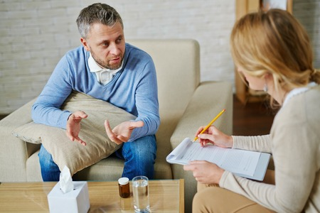 Man uit te leggen zijn psychologisch probleem voor de arts Stockfoto