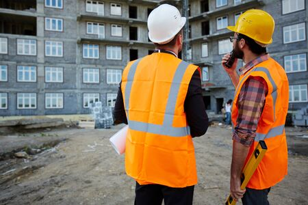 inspectors: Two inspectors looking at new building while discussing it Stock Photo