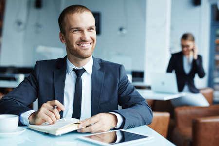 hombre escribiendo: feliz hombre de negocios la planificación del trabajo mientras se está sentado en el café