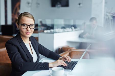 typing: Serio secretaria mirando la cámara mientras escribe