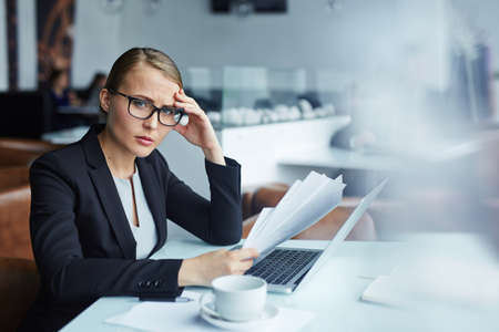 tense: Tense female holding business documents over laptop Stock Photo