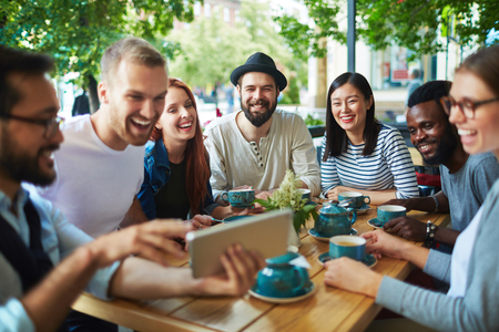 Group of happy friends looking at touchscreen held by one of them