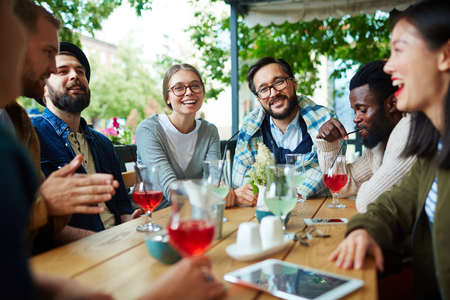 restful: Happy young people having friendly conversation in summer cafe