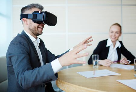 nonexistent: Modern businessman in virtual reality headset trying to touch something non-existent Stock Photo