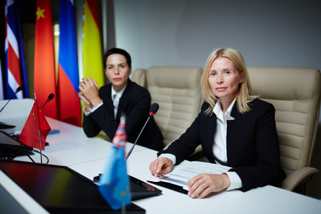 Two female politicians sitting at political conference