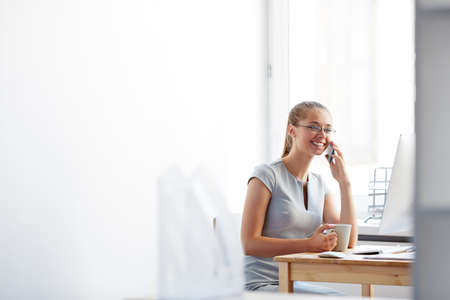work addicted: Busy woman talking on mobile phone during coffee break in office