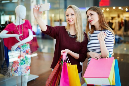 or spree: Two girls with paperbags making selfie during shopping