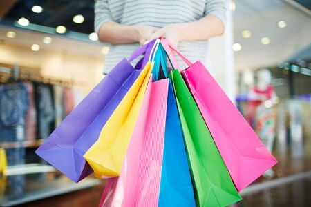 paperbags: Multi-color paperbags held by young modern shopper Stock Photo