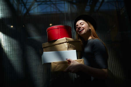 shopper: Laughing shopper carrying stack of boxes Stock Photo