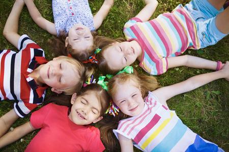 Relajan los niños con los ojos cerrados yace en el suelo