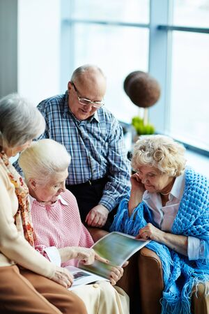 Group of friendly seniors looking through magazine or photo album in cafe Stock fotó