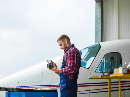 hangar: Young repairman in uniform working in hangar
