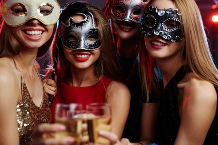 Young girls in masquerade masks toasting with champagne