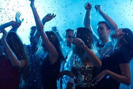 Ecstatic friends dancing in confetti in night club