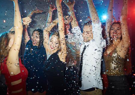 Ecstatic young men and women enjoying dance party