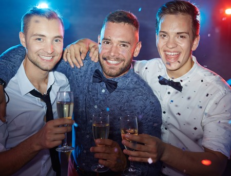 clubber: Three elegant guys with champagne looking at camera at party