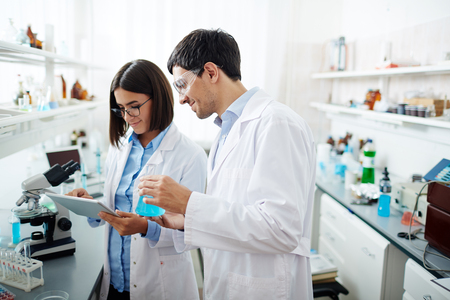chemical substance: Two scientists browsing for characteristics of new chemical substance