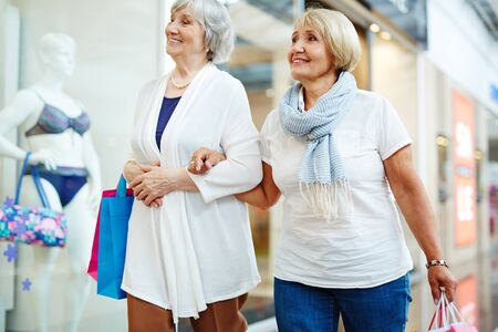 Mature friends with paperbags passing by shop window Stock Photo