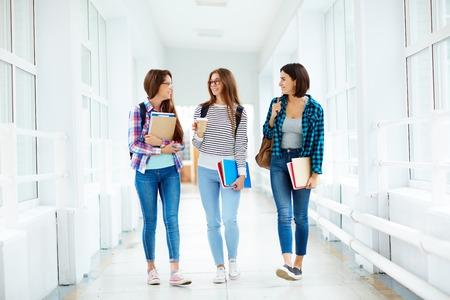 niñas felices que recorren abajo del pasillo de la universidad a la rotura Foto de archivo