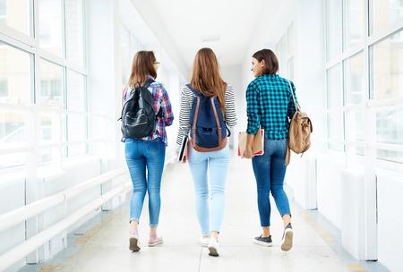 estudiantes lindo con mochilas caminando por el pasillo de la universidad