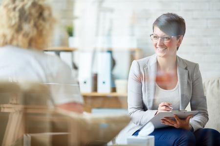 Šťastný psycholog poslouchat její problém pacienta Reklamní fotografie