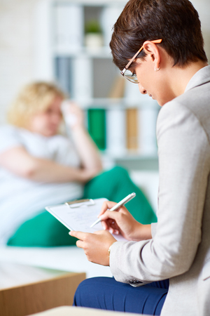 Psychologist making notes while listening to her patient
