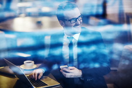 people on computers: Smiling businessman working on laptop at cafe Stock Photo