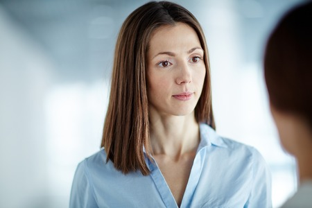attentively: Young businesswoman listening to her partner attentively