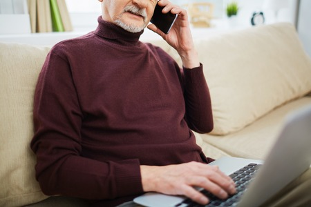 wireless telephone: Senior man sitting on sofa and using his laptop and talking on the phone