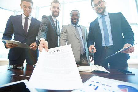 suggesting: Group of business people suggesting you to sign a contract
