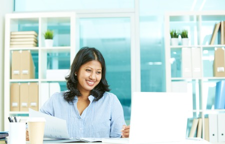 casual office: Smiling young businesswoman working with laptop