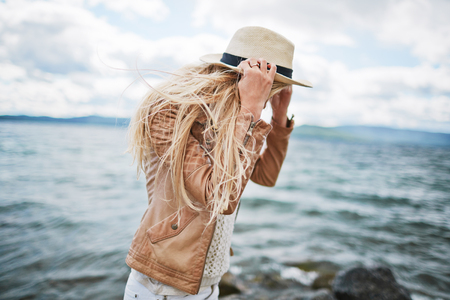 Young blonde in hat spending time on the beach photo