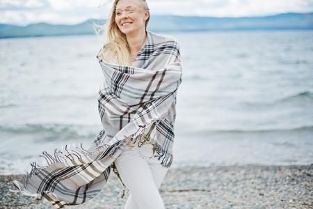 Woman in blanket walking on seaside photo