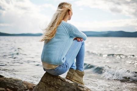 Rückansicht der jungen Frau am Meer am Strand sitzen