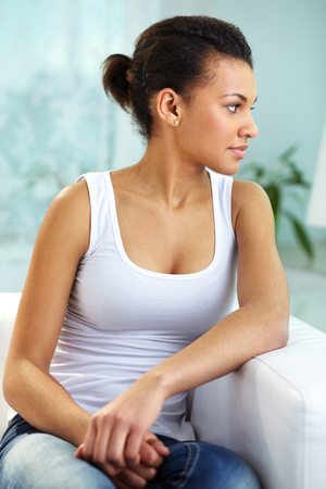 Young woman sitting on sofa and thinking about something photo