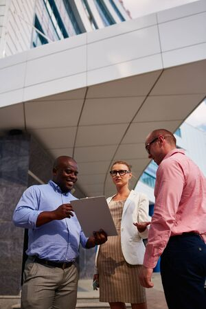 Group of business people standing and communicating outdoors photo