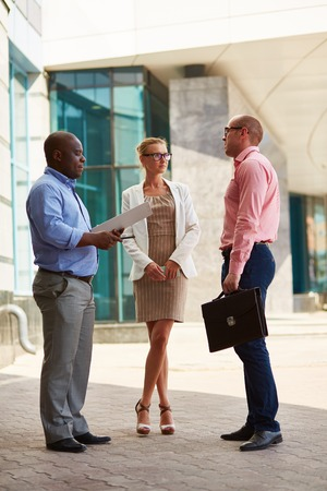 Group of business people talking outdoor in an urban setting photo