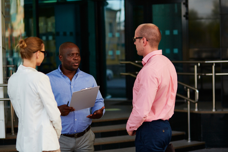 African businessman explaining something to his partners outdoors photo
