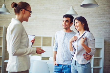 estate: Female estate agent giving young couple key from real estate Stock Photo