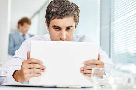 businesspersons: Pensive businessman sitting at the table with laptop Stock Photo