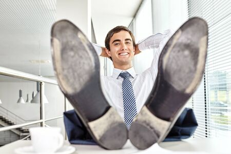 feet on desk: Satisfied businessman sitting by desk at office with feet on table