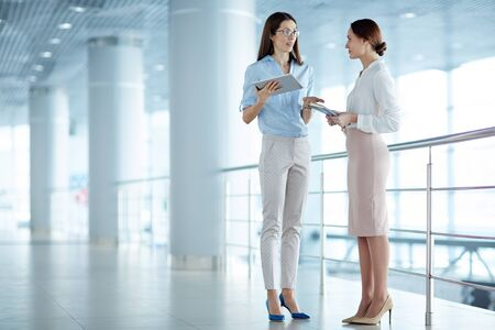 standing together: Female leader communicating with secretary at office