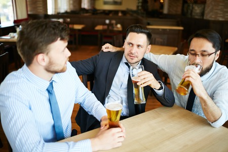 formally: Three tired formally dressed business man relaxing and having beer in bar after work.