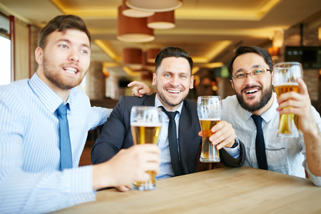 formally: Three formally dressed businessmen in ties with beaming smiles looking at camera celebrating success with beer in bar.