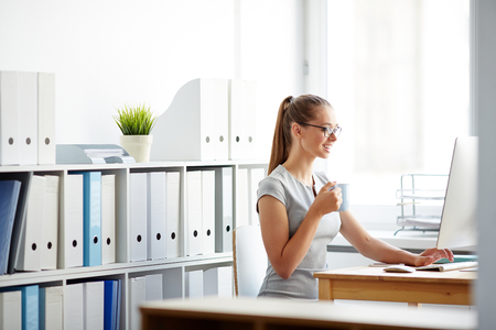 Young attractive businesswoman typing, chatting online or telecommunicating, alone in light spacious room