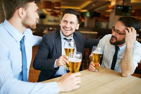 Shot of two Caucasian and one Asian business partners in formal attire laughing and enjoying beer in bar after work.