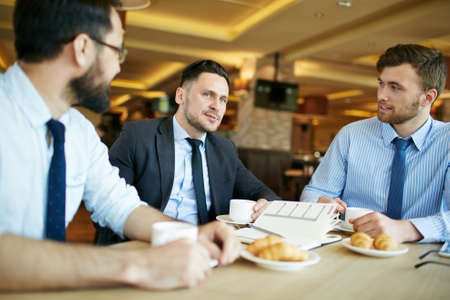 formally: Three relaxed formally dressed businessmen on a casual business meeting in cafe having coffee with croissants and discussing work.