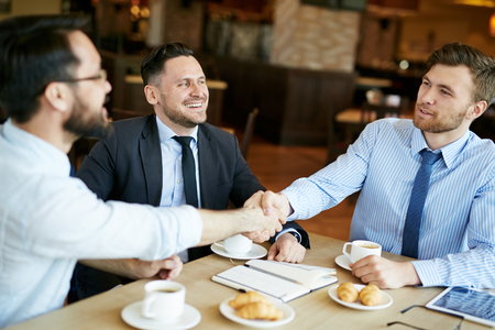 formally: Two formally dressed pleased businessmen in shirts on casual meeting in cafe sharing coffee and shaking hands in agreement over deal, another coworker in suit looking happy.